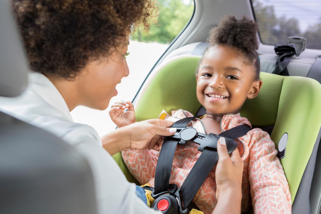 Mãe ajeita o cinto da cadeirinha infantil na filha já dentro do carro