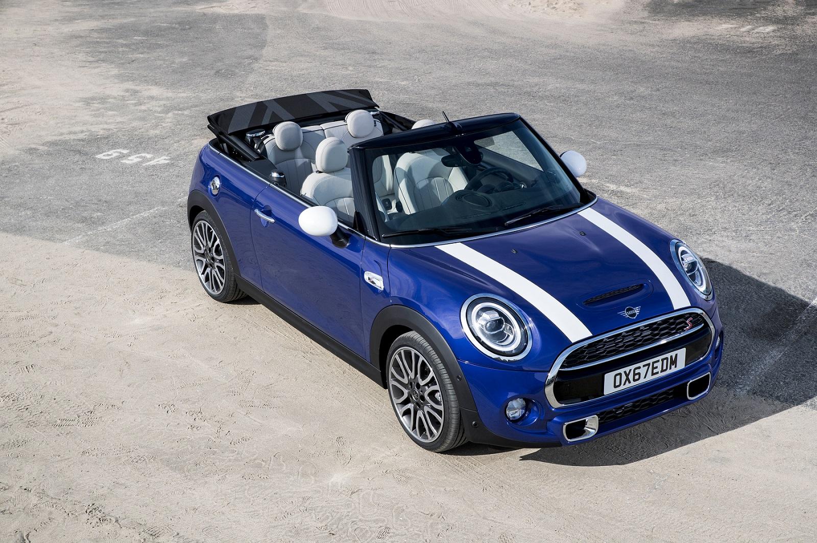 Mini Cooper Cabrio S visto do alto na cor azul, com duas faixas brancas sobre o capô e capota aberta