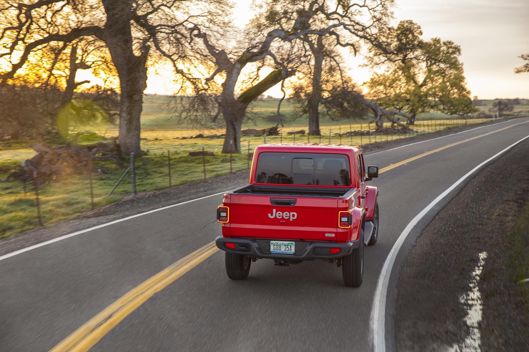Jeep Gladiator Overlandha de traseira fazendo uma curva na estrada