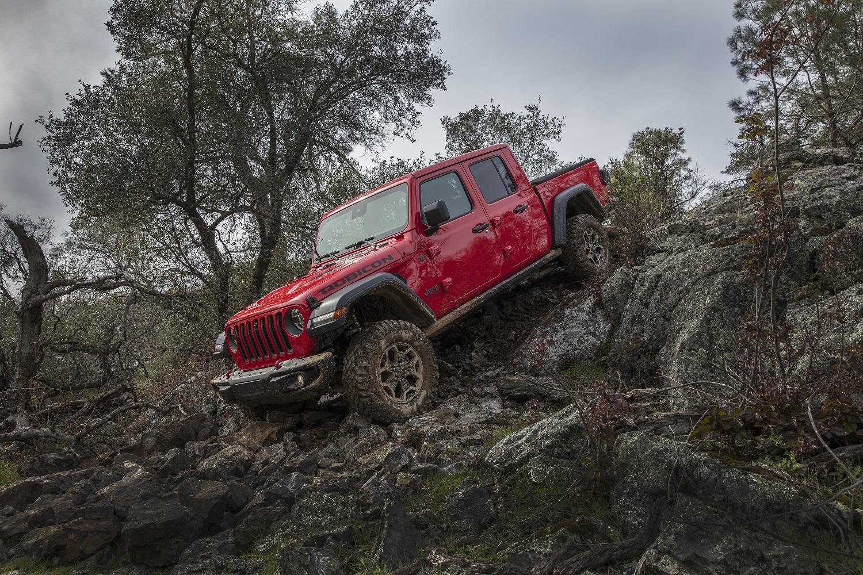 Jeep Gladiator vermelha descendo um terreno acidentado entre rochas e com muita lama