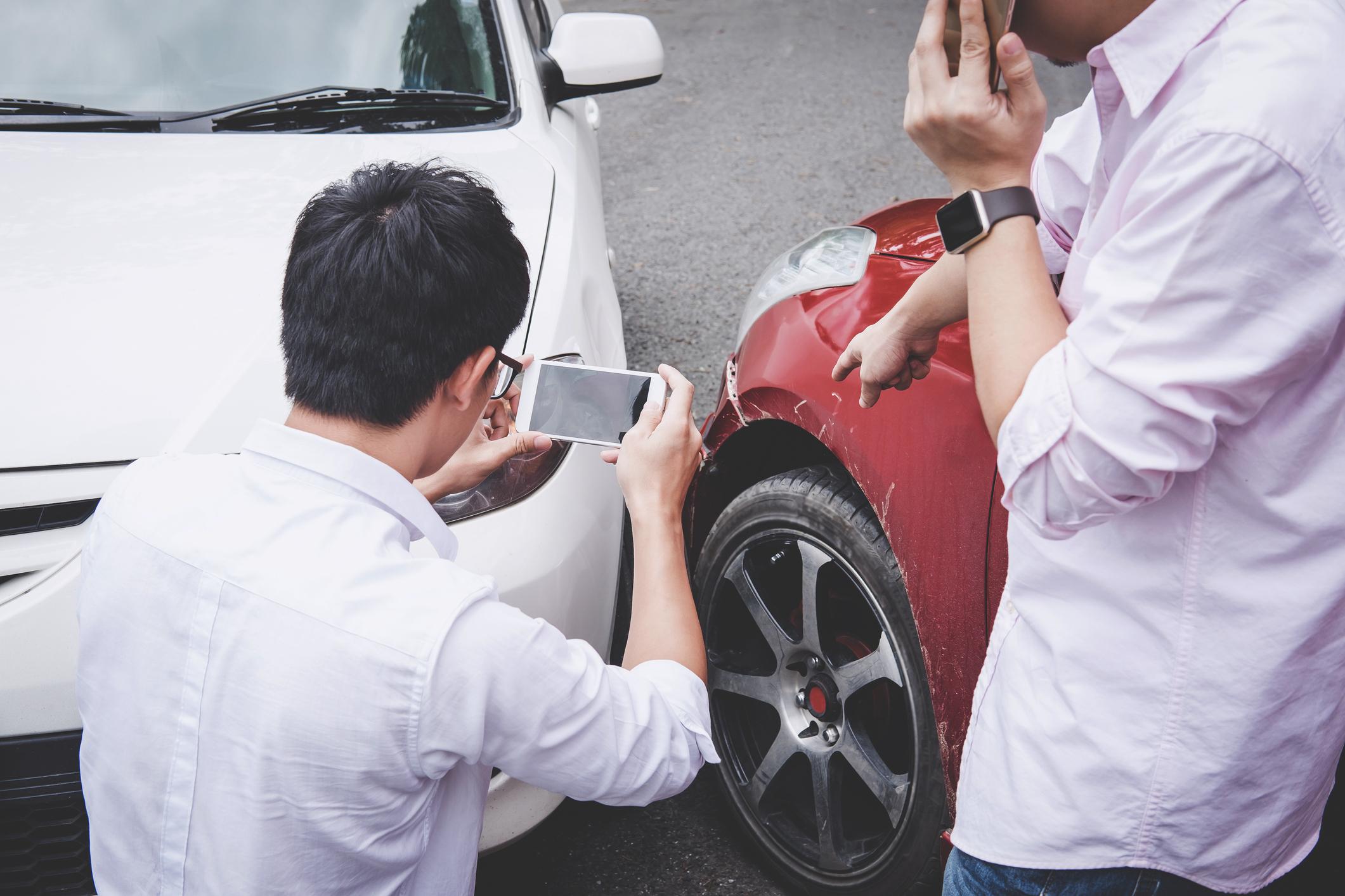 Dois homens discutindo por uma batida de carro, um está tirando foto com o celular