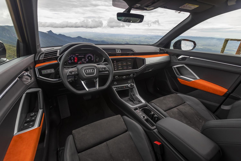 Audi Q3 com volante de base reta, detalhes de couro laranja nas portas e no painel