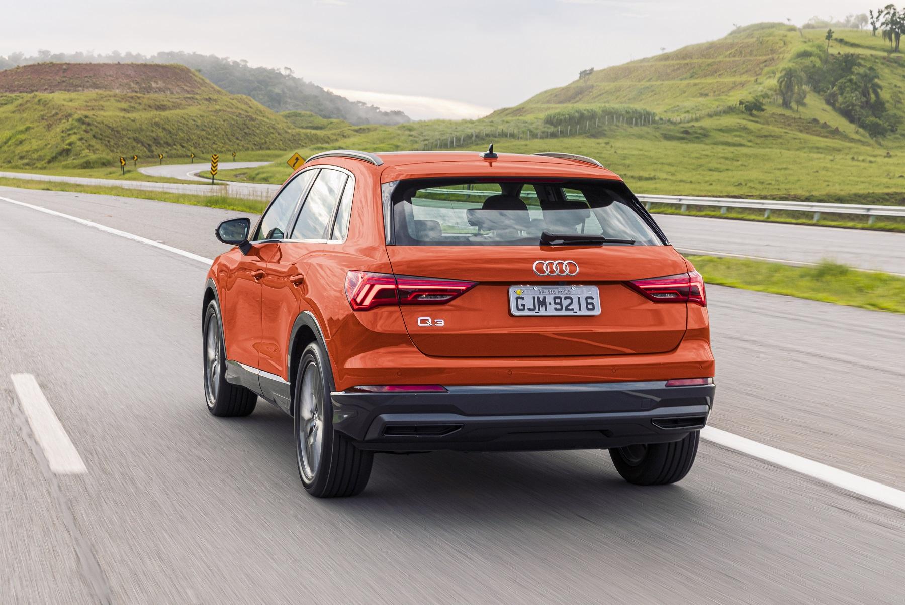Audi Q3 laranja de traseira em movimento na estrada