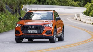Audi Q3 laranja em movimento na curva e ao fundo a estrada sinuosa