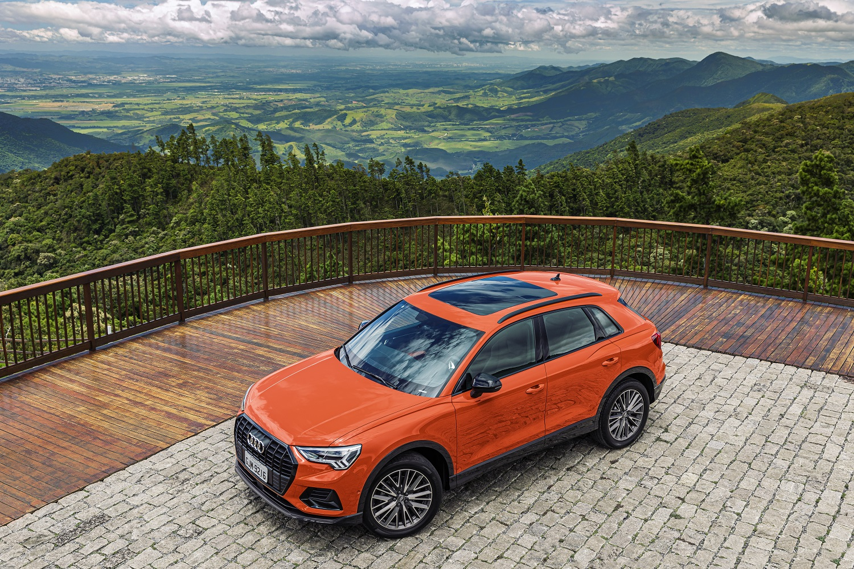 Audi Q3 laranja parado visto de cima com teto-solar e ao fundo um vale cercado de verde