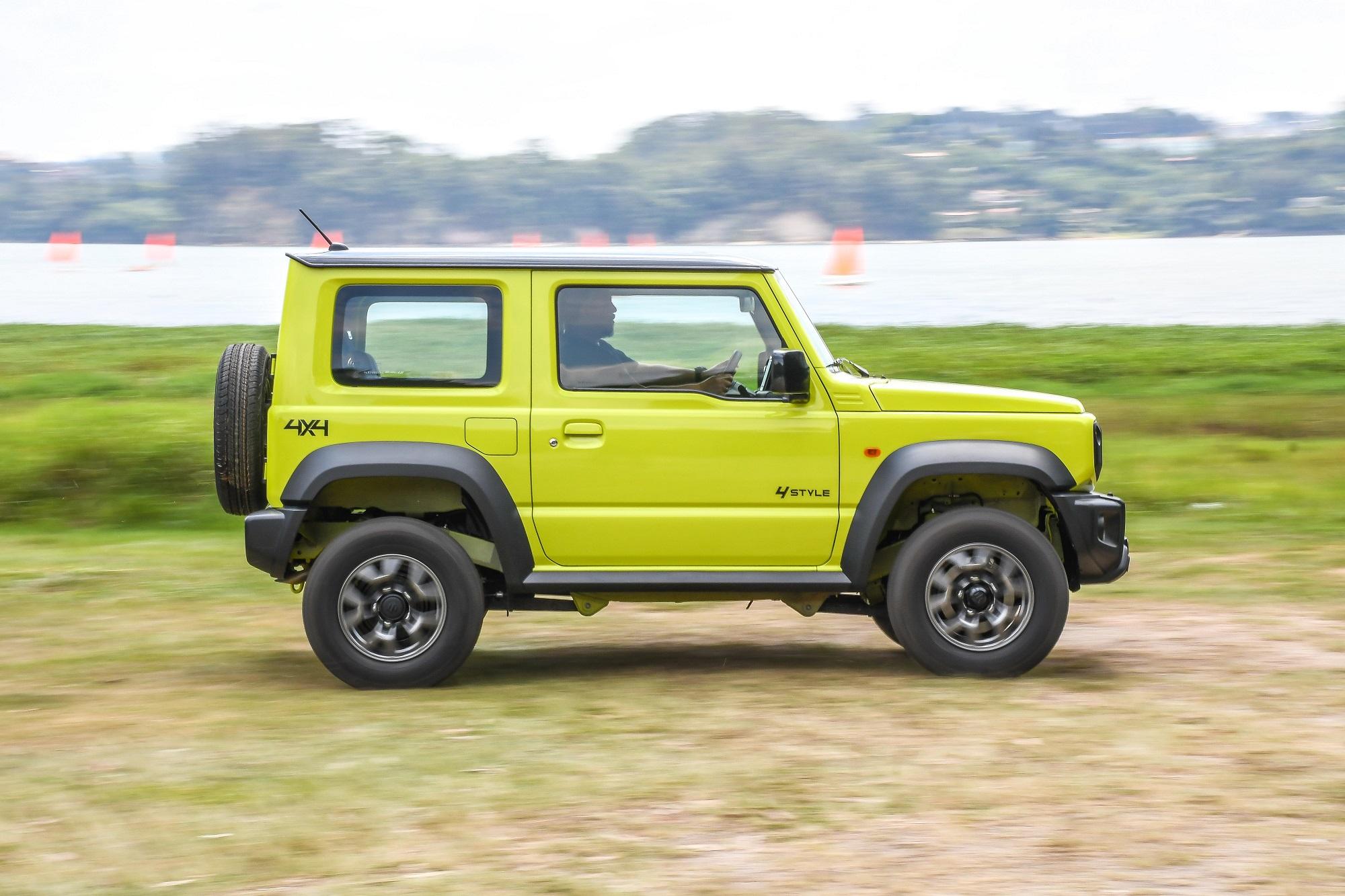 Suzuki Jimny verde de perfil em movimento na grama