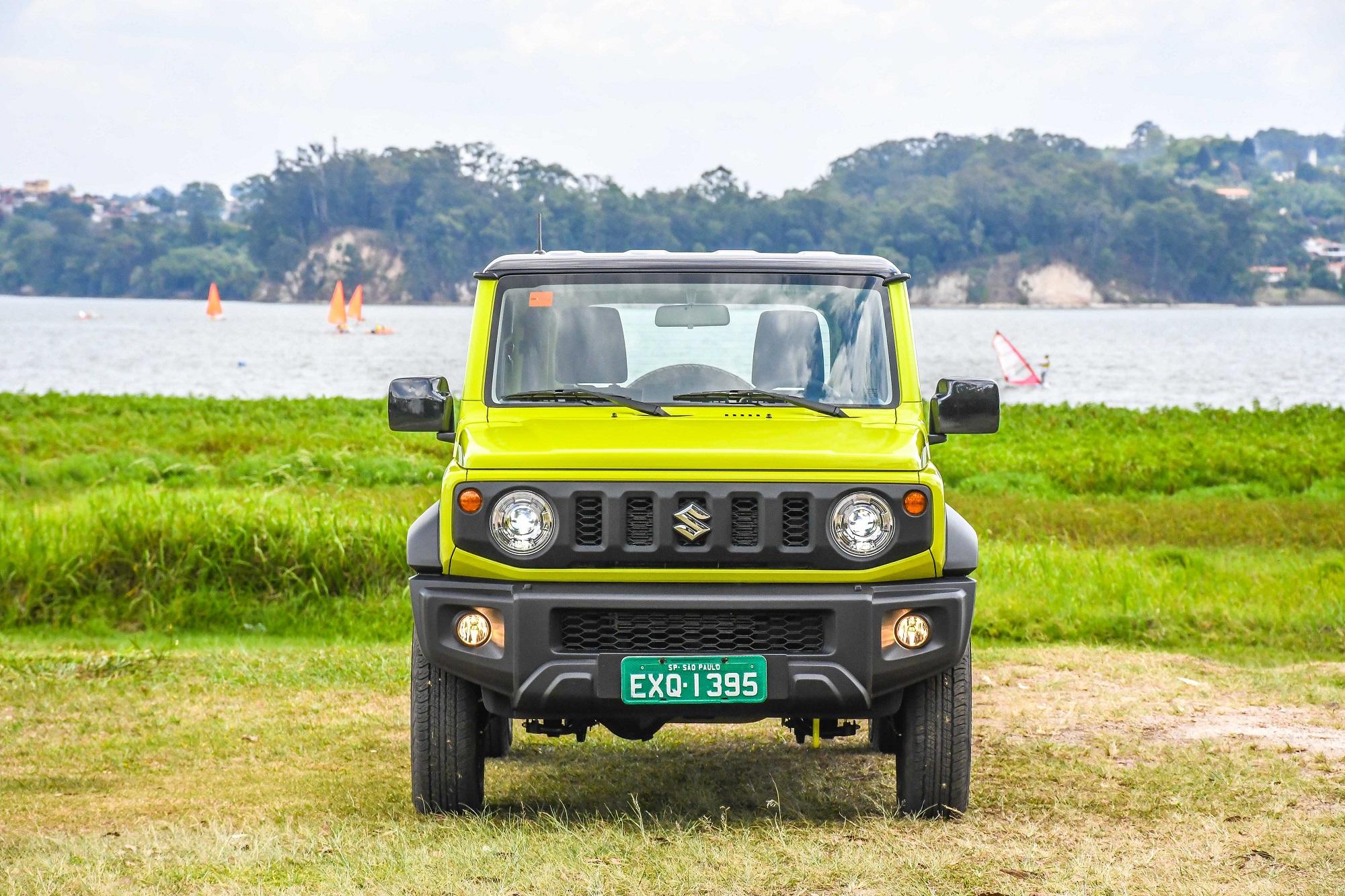 Suzuki Jimny 4style na cor verde limão de frente em um terreno de terra e graama