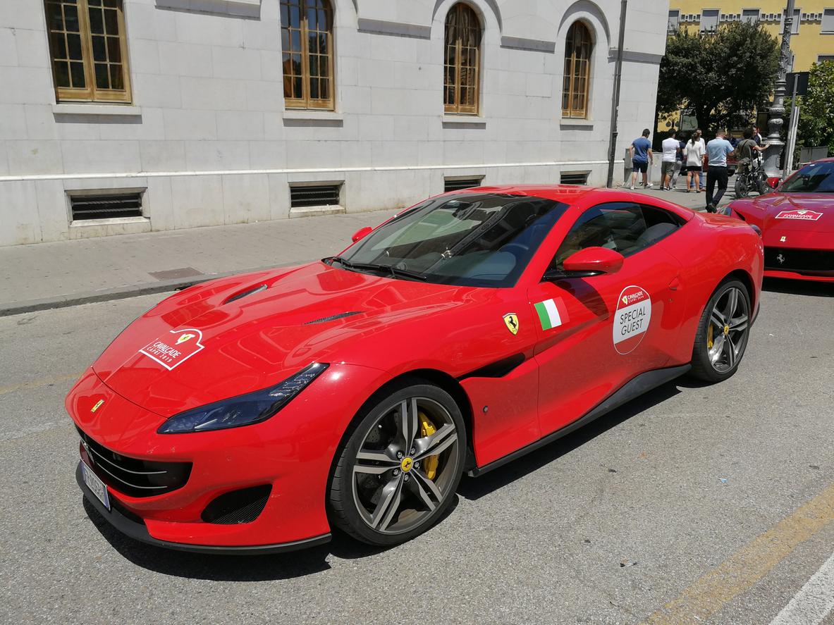 Ferrari Portofino vermelha vista na diagonal e ambientada em um cenário urbano europeu