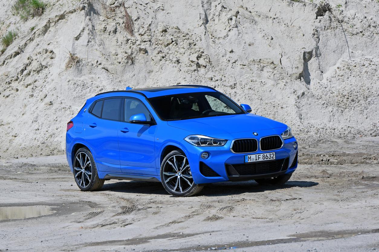 BMW X2 azul visto na diagonal e ambientadona estrada