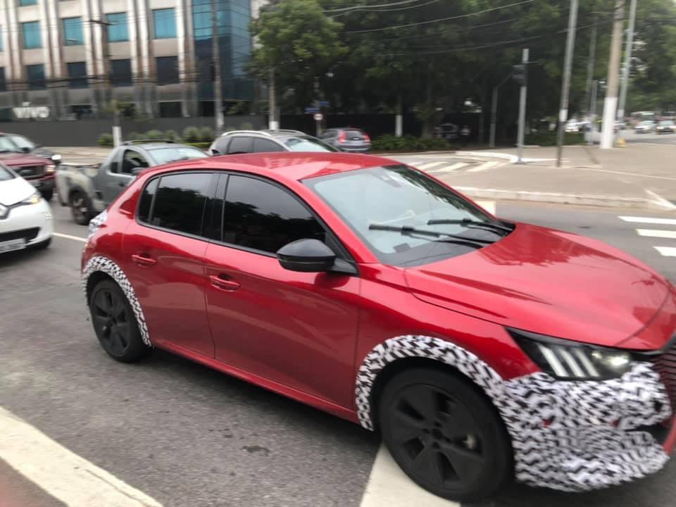 Peugeot 208 vermelho rodando na cidade de São Paulo com adesivos nos para-lamas e no para-choques e com os faróis com três barras verticais de leds