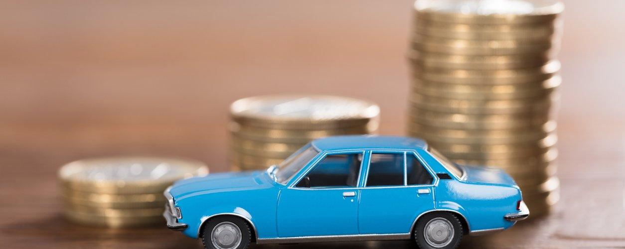 carrinho de brinquedo azul em frente a uma pequena pilha de moedas em cima da mesa