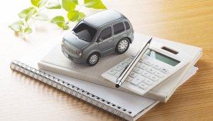 carrinho de brinquedo cinza ao lado de calculadora branca e, ambos, em cima de um pequeno caderno de anotações