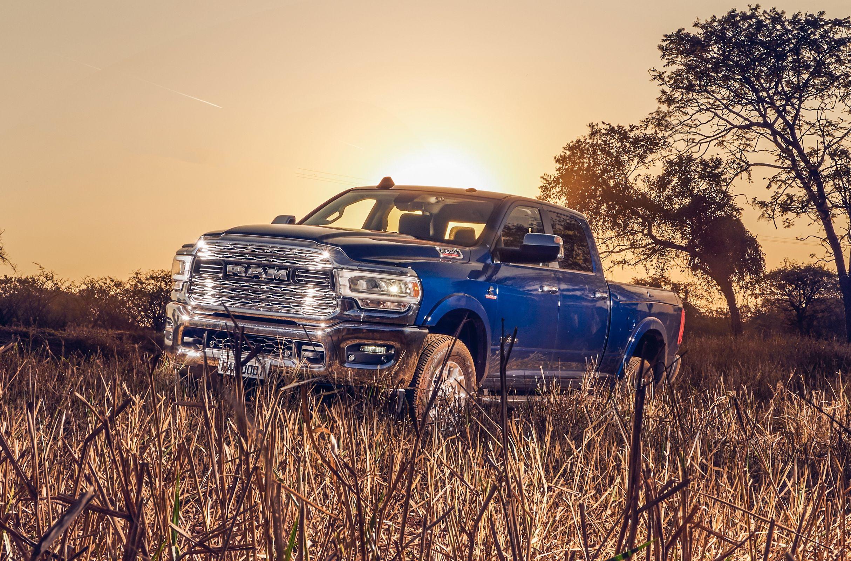 Ram 2500 na cor azul de frente parcialmente coberta pelo mato e ao fundo árvores e o pôr do sol