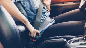 mulher no banco do motorista colocando o cinto de segurança