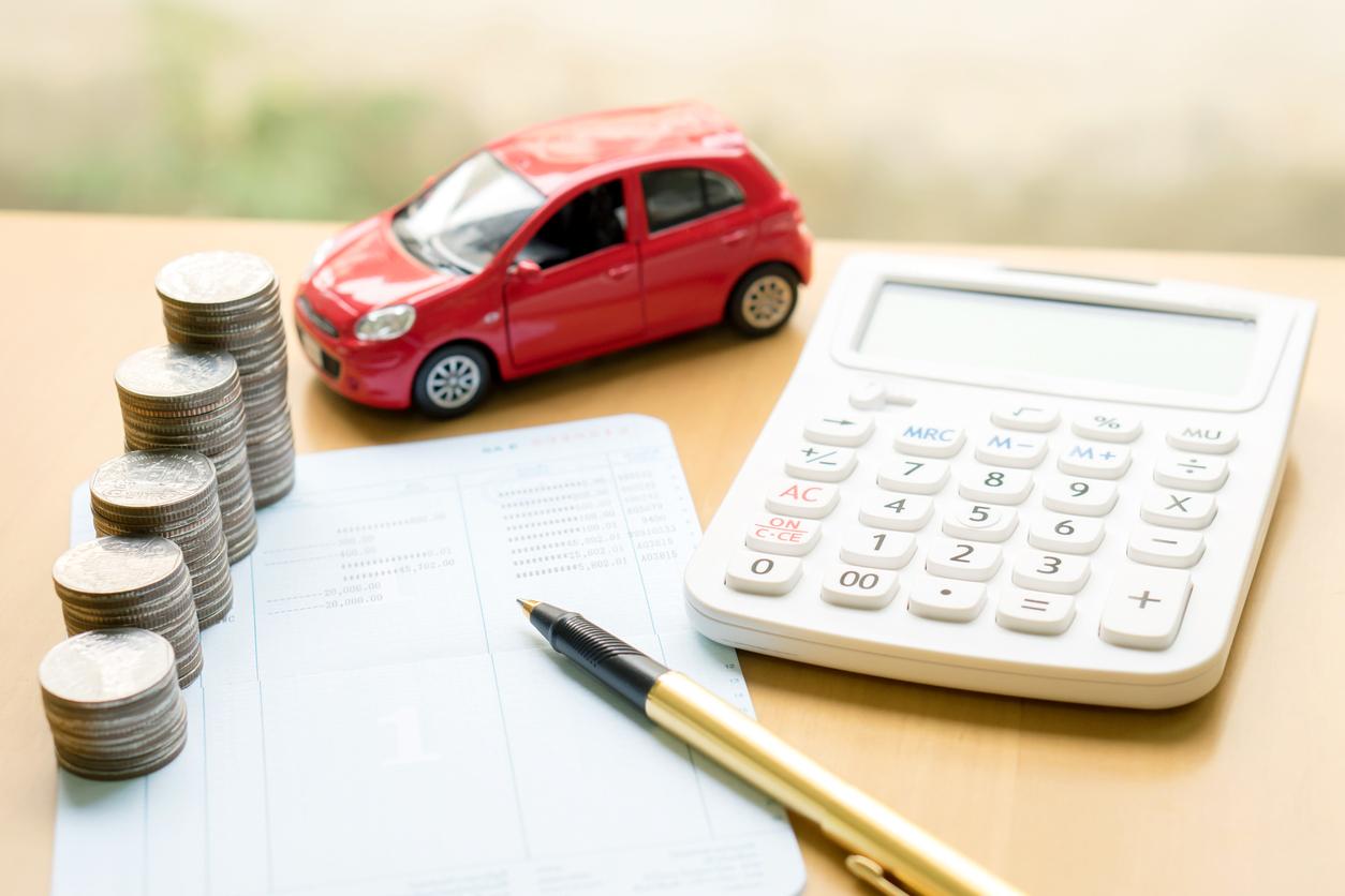 Caderno de anotações com uma pilha de moedas em cima, além de caneta, calculadora e um carrinho vermelhor de brinquedo