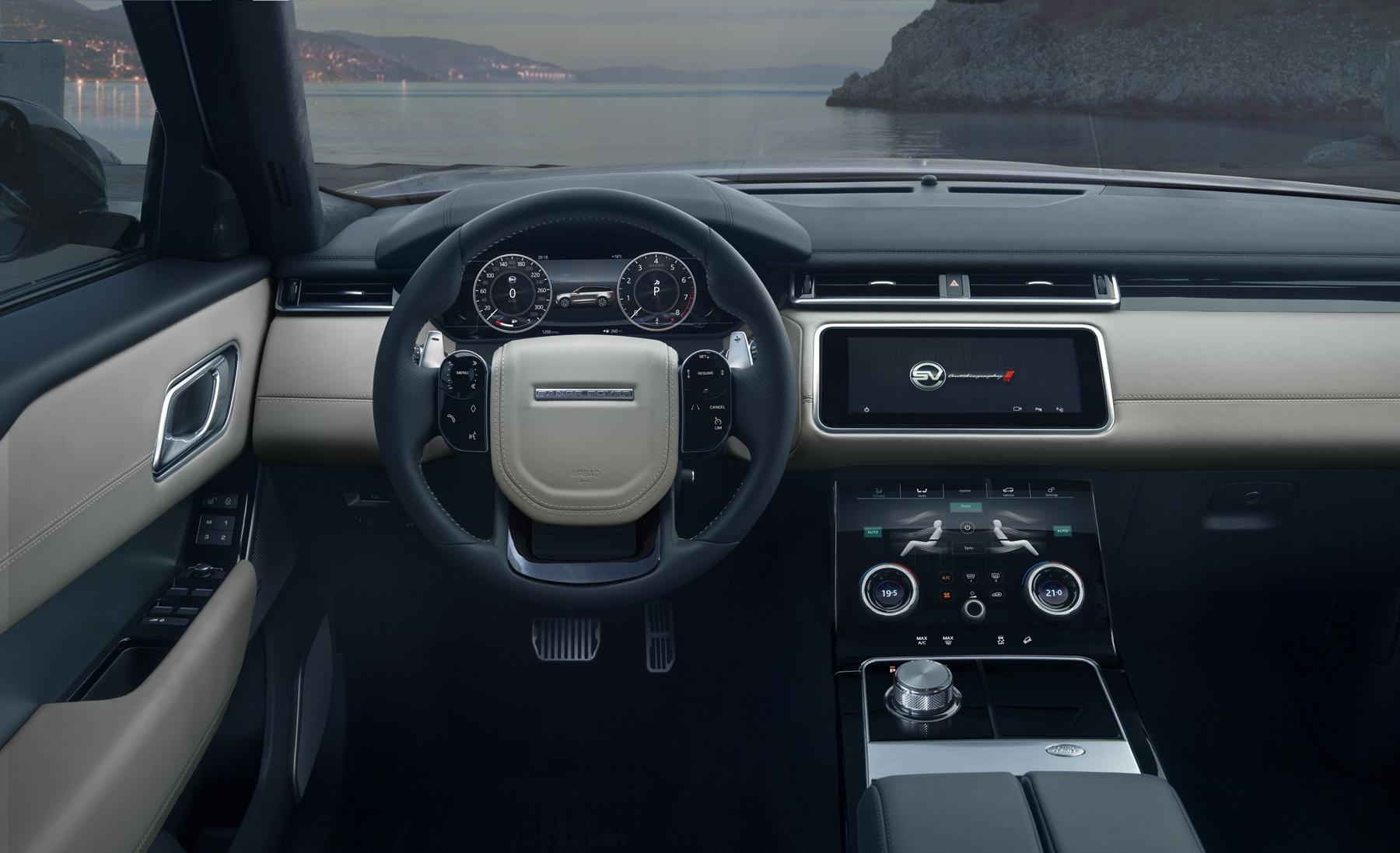 Cabine do Range Rover Velar com partes claras de couro no painel e volante esportivo com costuras aparentes