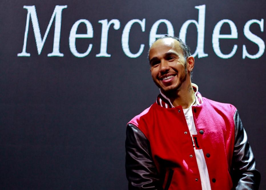 Lewis Hamilton, piloto da Mercedes, posa sorridente para a foto em um painel ao fundo com a palavra Mercedes