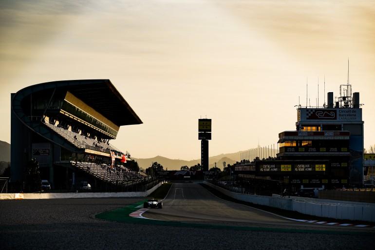 Circuito de Barcelona no fim de tarde com carro na tomada de curva durante os testes e arquibancada, boxes e torre ao fundo