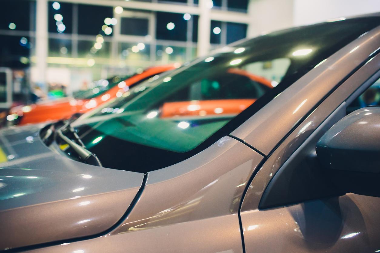 Foto mostra parte de para-brisa do carro e ao fundo outros veículos em exposição em uma concessionária