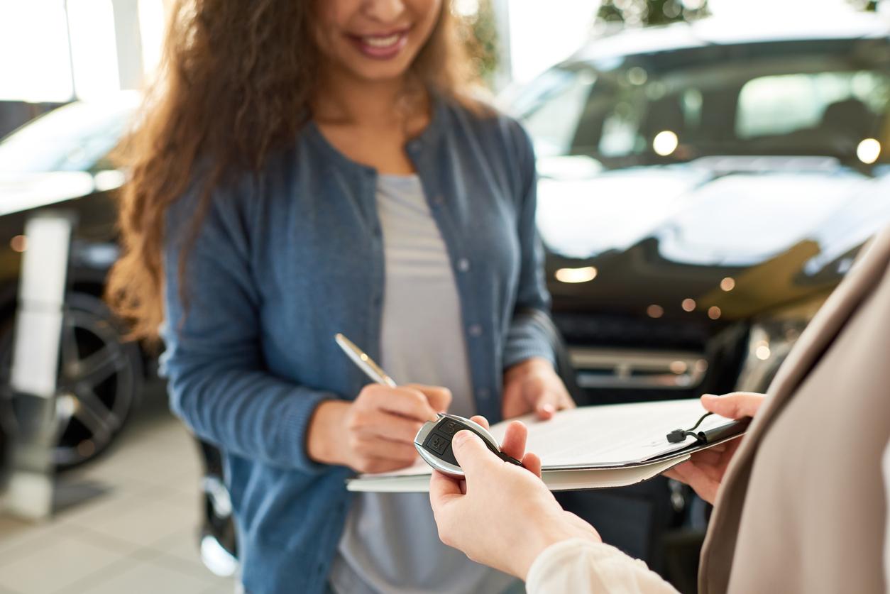 Mulher preenche ficha enquanto vendedor entrega chave de carro para ela em uma loja de automóveis