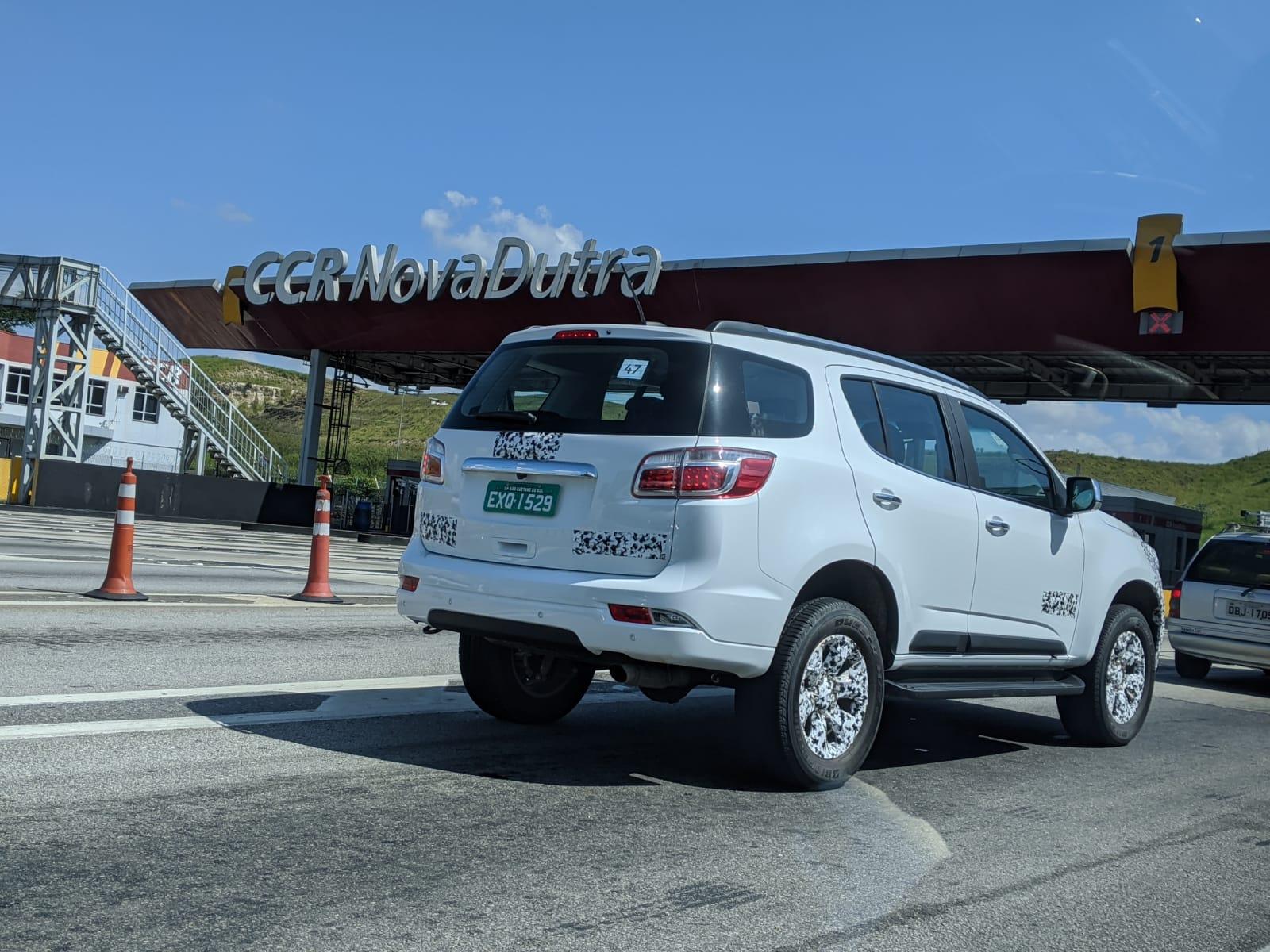 Chevrolet Trailbçazer branbco de traseira parado na fila do pedágio da Via Dutra com adesivos apenas nos nomes do carro e no emblema da Chevrolet