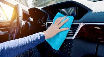 Foto mostra mão de uma pessoa passando um pano azul sobre a central multimídia de um veículo