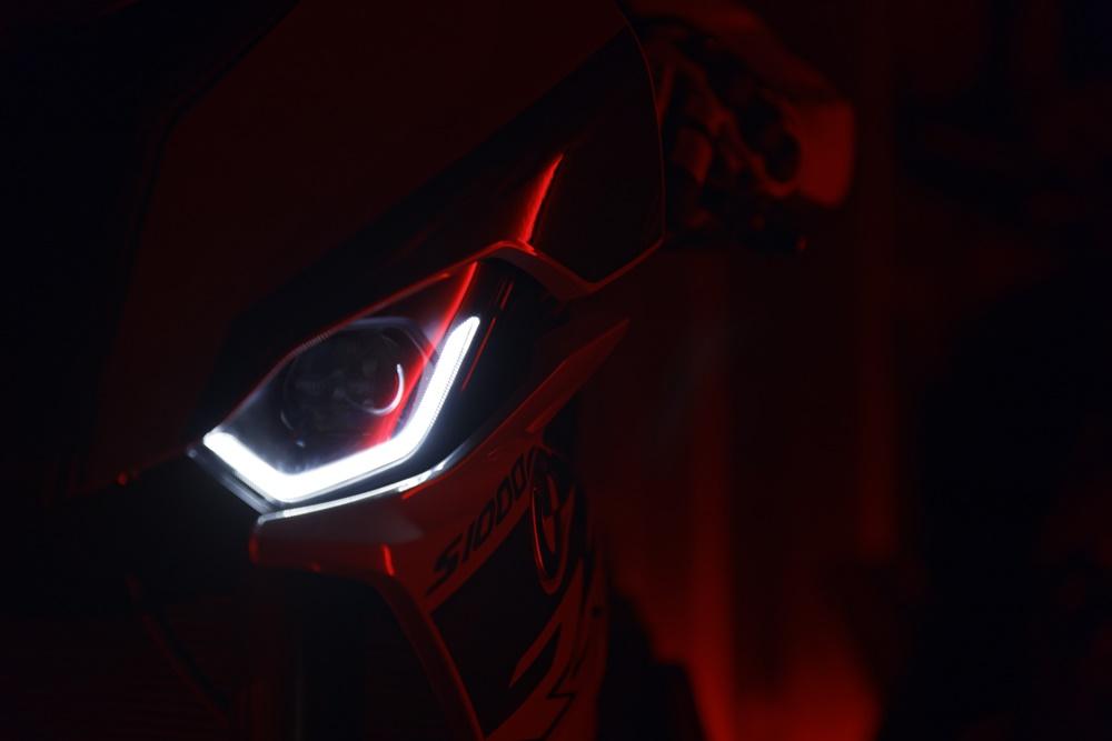 Detalhes dos faróis de LEDs acesos dentro das lentes da moto em um ambiente escuro
