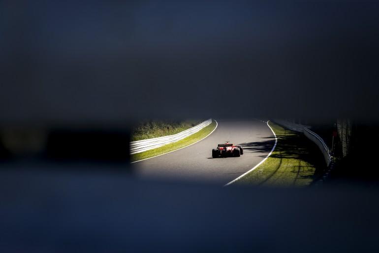 Foto de um carro de fórmula um no GP do Japão tirada da abertura de um guard rail