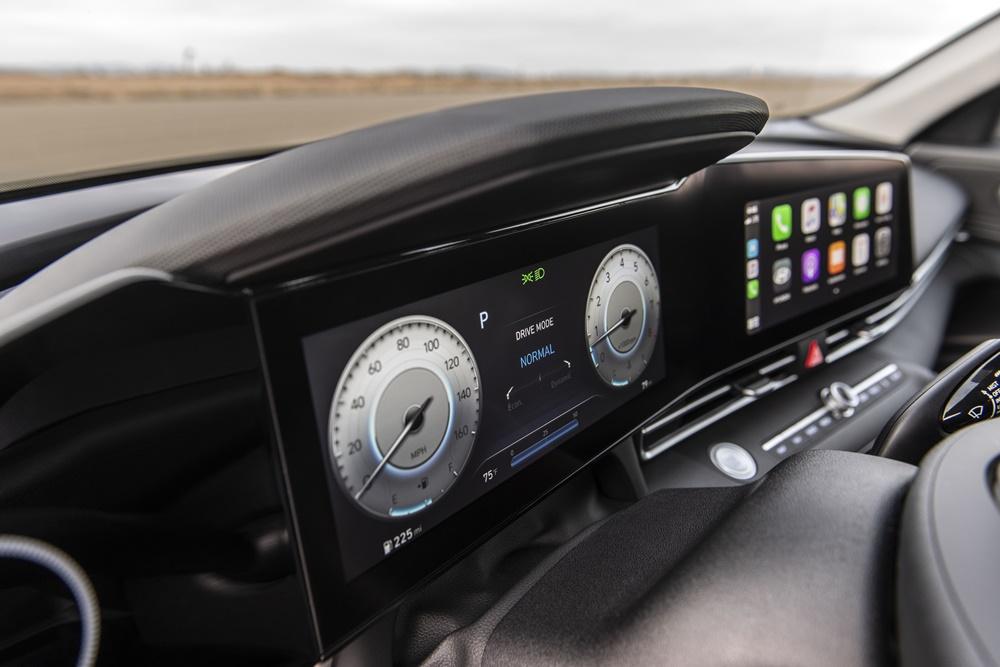 Foto mostra a tela do quadro de instrumentos configurada para velocímetro e conta-giros redondos em forma analógica e ao lado a tela da central multimídia