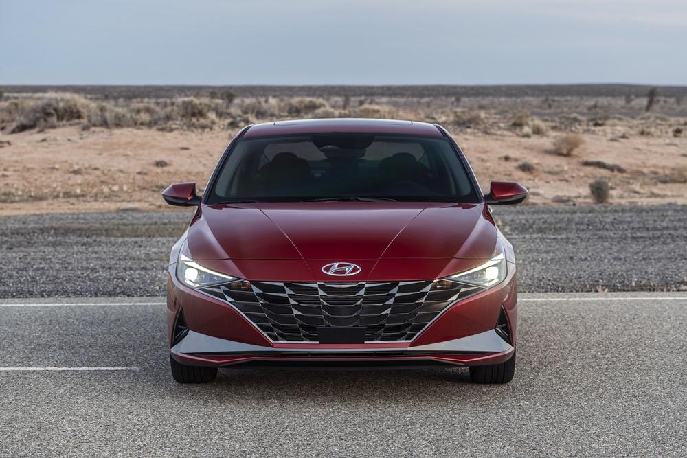 Novo Hyundai Elantra vermelho estacionado de frente tem grade rebaixada em forma de sorriso e lanternas que lembram bumerangues e se propagam pelas extremidades do carro