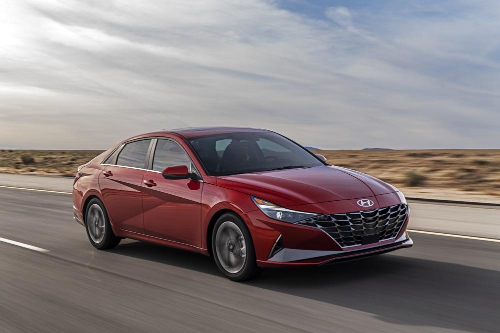 Novo Hyundai Elantra na cor vermelha em movimento na estrada ao fundo paisagem de deserto