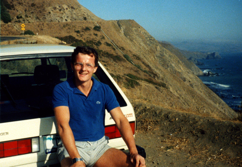 Derek Pratt sentado no para-choque traseiro do seu Volkswagen Golf Gti original branco e ao fundo montanhas e um vale