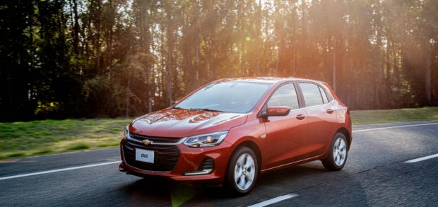 Chevrolet Onix vermelho em movimento na estrada com sol baixo atrás de uma plantação de eucalliptos