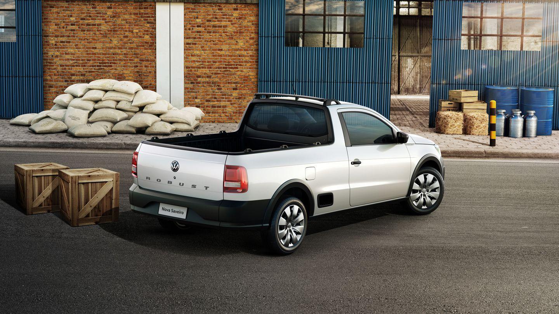 Volkswagen Saveiro Robust cabine simples de traseira vista do alto com galpão ao fundo e uma pilha de sacos de cimento ao lado