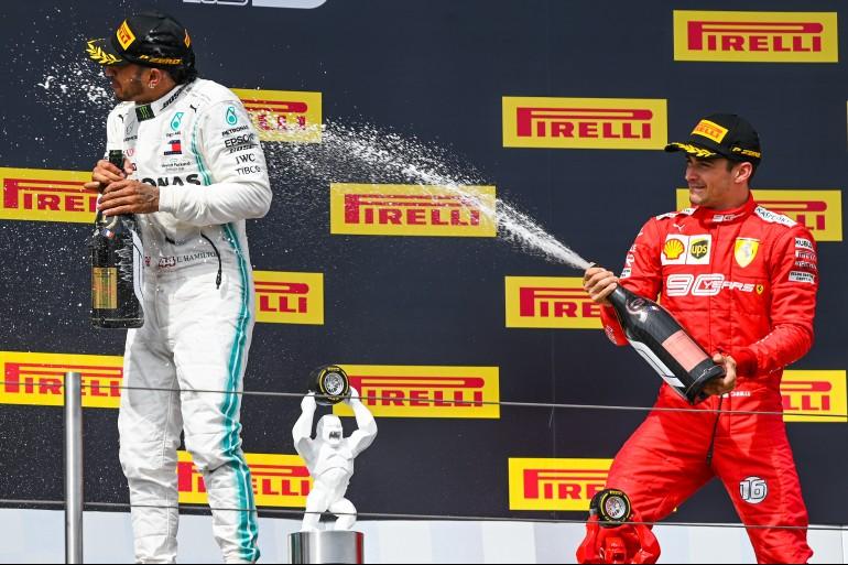 Charles Leclerc, de macacão vermelho da Ferrari no terceiro lugar do pódio do Gp Da França 2019 espirra champanhe em Lewis Hamilton, de macacão branco da Mercedes, no lugar mais alto do pódio