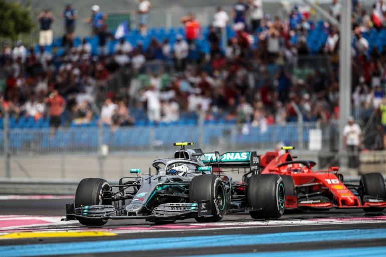 Carro de F1 da Mercedes faz a curva com carro da Ferrari colado durante prova da Fórmula 1