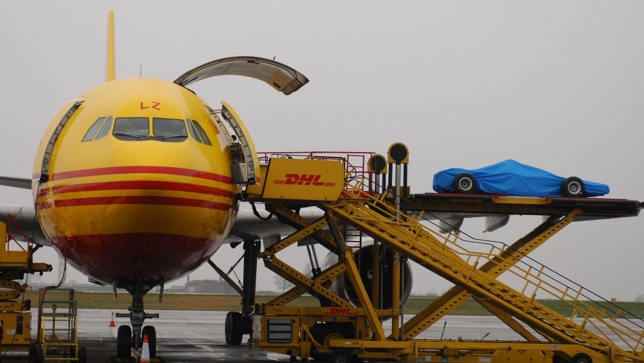 Carro de Fórmula 1 coberta embarca em avião de carga amarelo da DHL