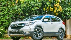 Honda CR-V branco de frente com árvores ao fundo