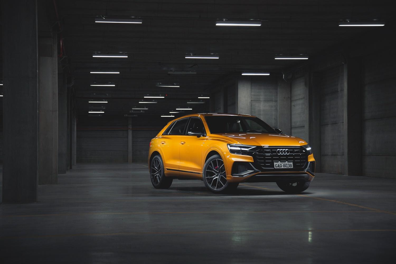 Audi Q8 dourado de frente em um estacionamento com piso cinza, pilastras ao fundo e luzes no teto