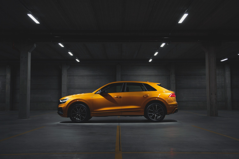 Audi Q8 de perfil no estacionamento na cor doyrado