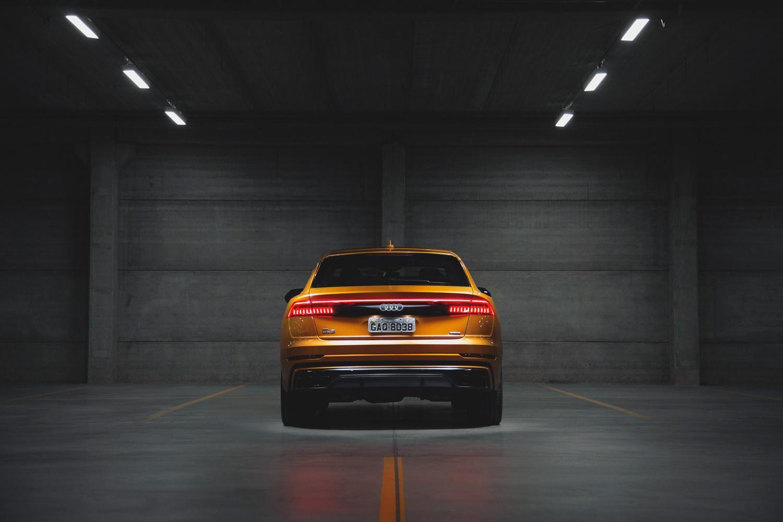 Audi Q8 dourado de traseira em um estacionamento coberto