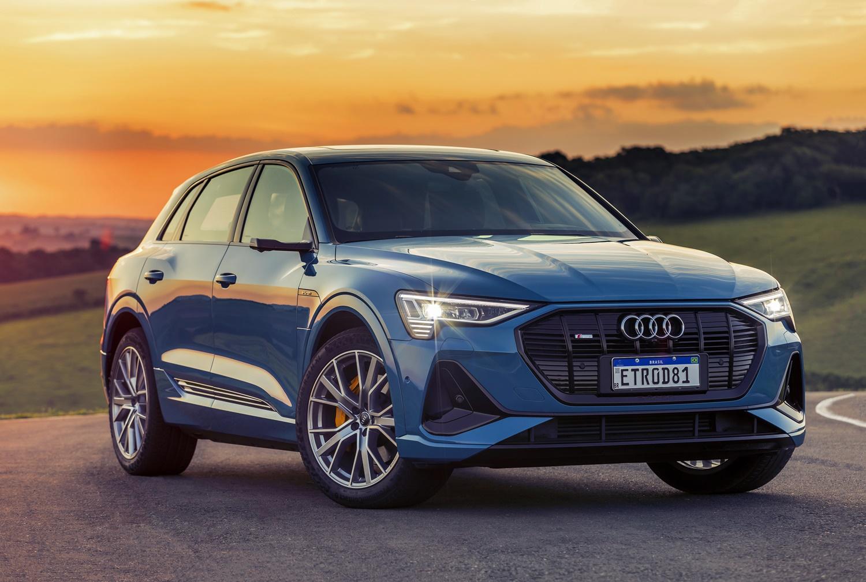Audi E Tron azul de frente com faróis acesos ao fundo entardecer atrás das montanhas