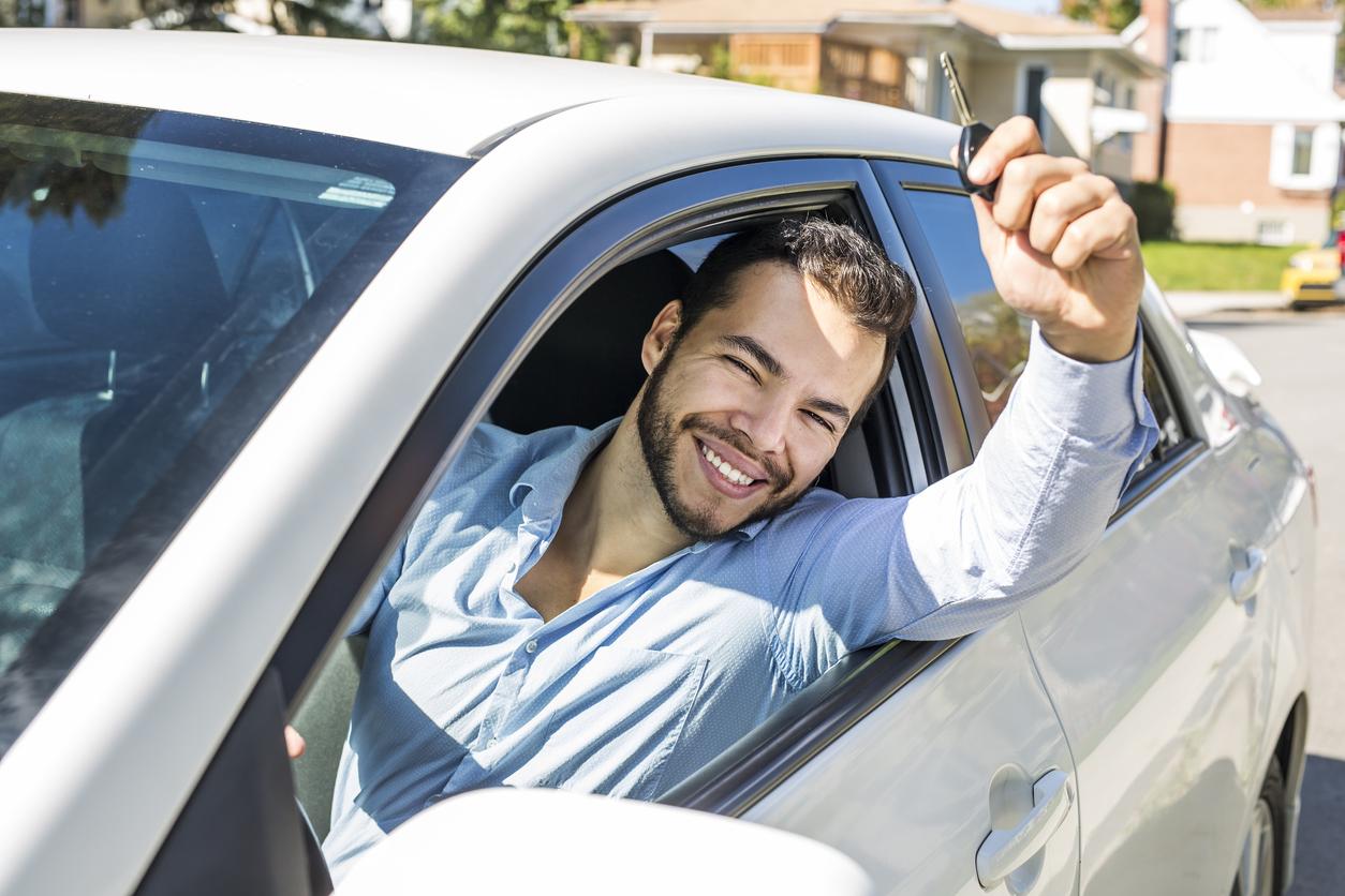 Homem da janela do carro com mão levantada e a chave do automóvel na mão