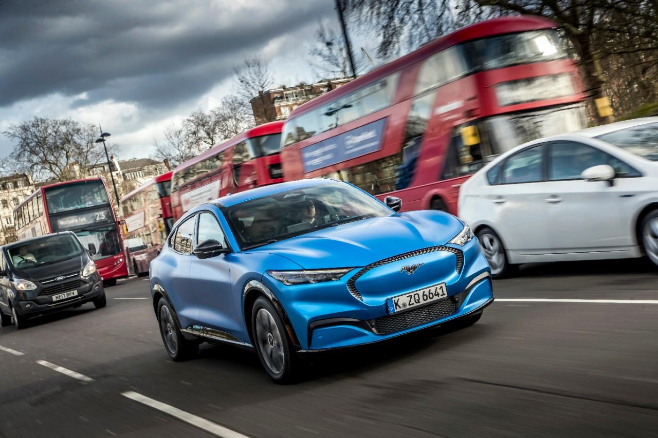 Mustang mach E azul em movimento em uma rua de Londres ao lado de um ônibus tradicional de dois andares