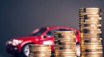 Imagem mostra pilha de moedas em primeiro plano com um carinho miniatura vermelho desfocado ao fundo para uilustrar omo economizar no seguro do automóvel?