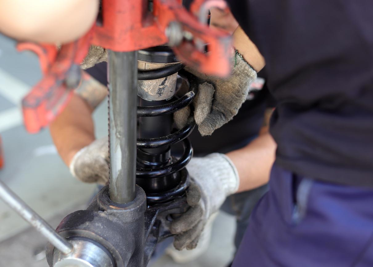 Amortecedor de carro gasto com mecânico fazendo os consertos