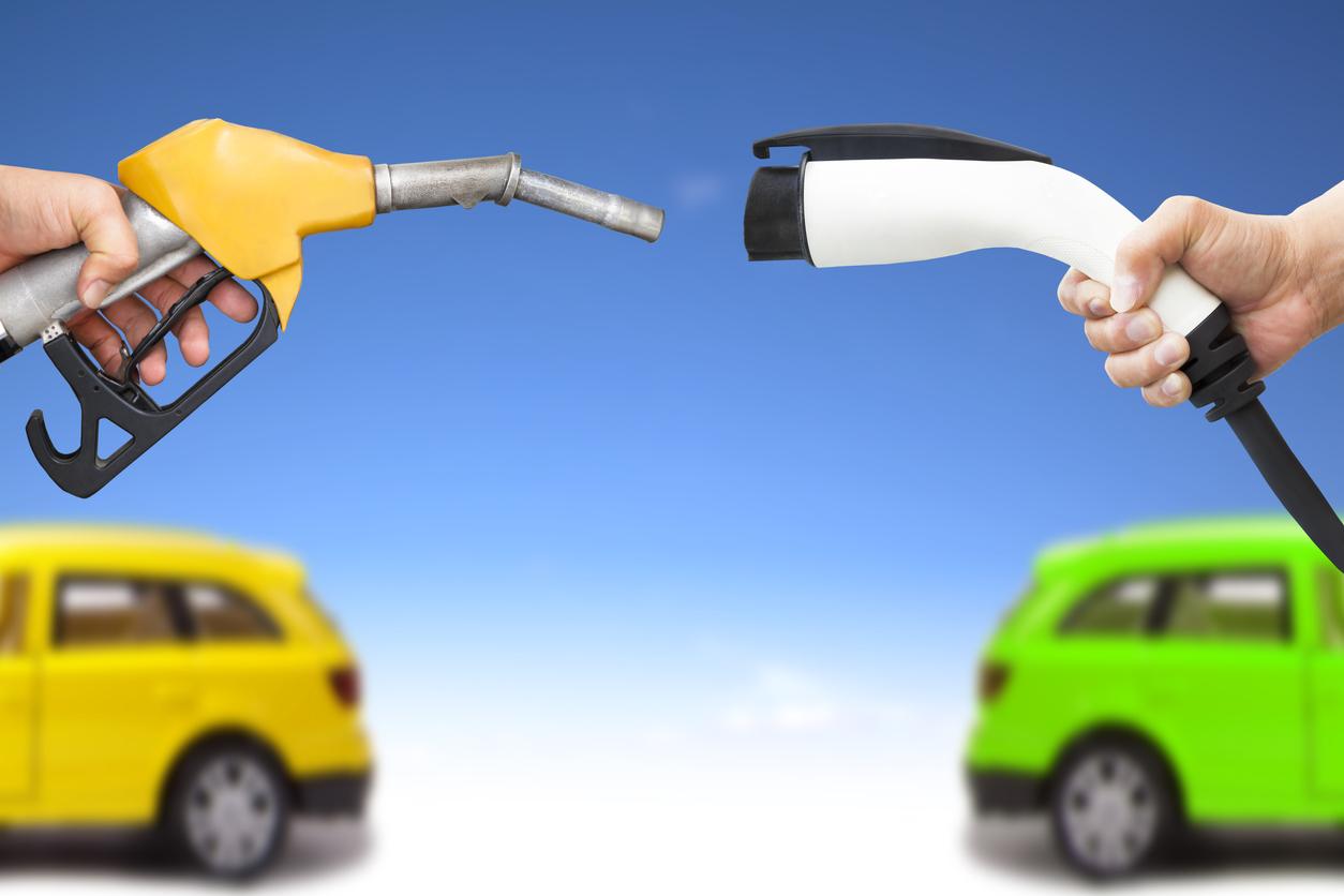Monatem mostra um bico de bomba de gasolina amarelo de frente para um soquete de carregamento de carro elétrico branco ao fundo a traseira de um carro amarelo e a tarseira de um carro verde, ambos desfocados