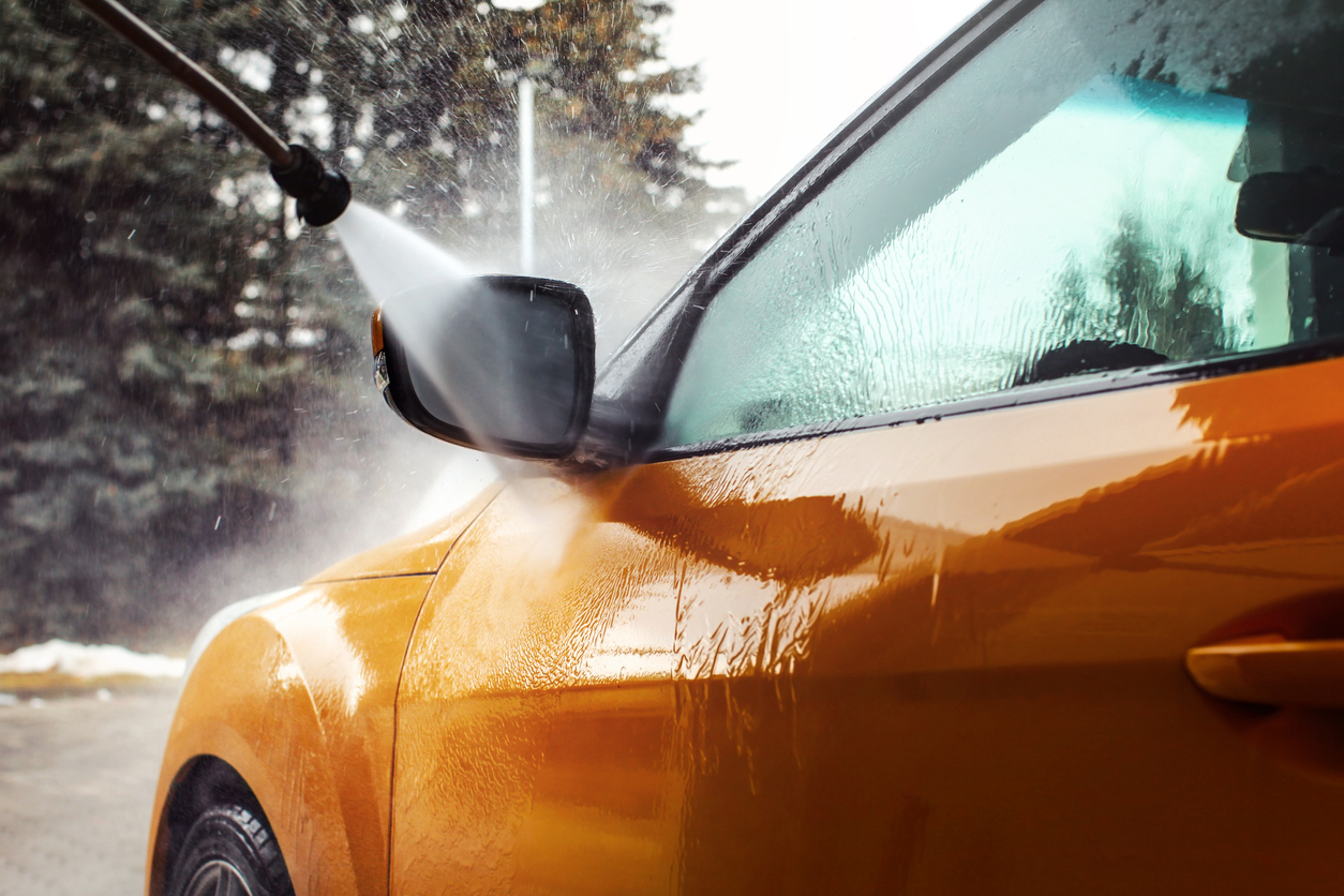 Detail On Dark Yellow Car Front Mirror Being Washed With Jet Water Stream In Carwash.