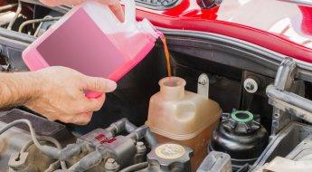 Homem coloca água com aditivo de coloração rosa no reservatório de água do carro