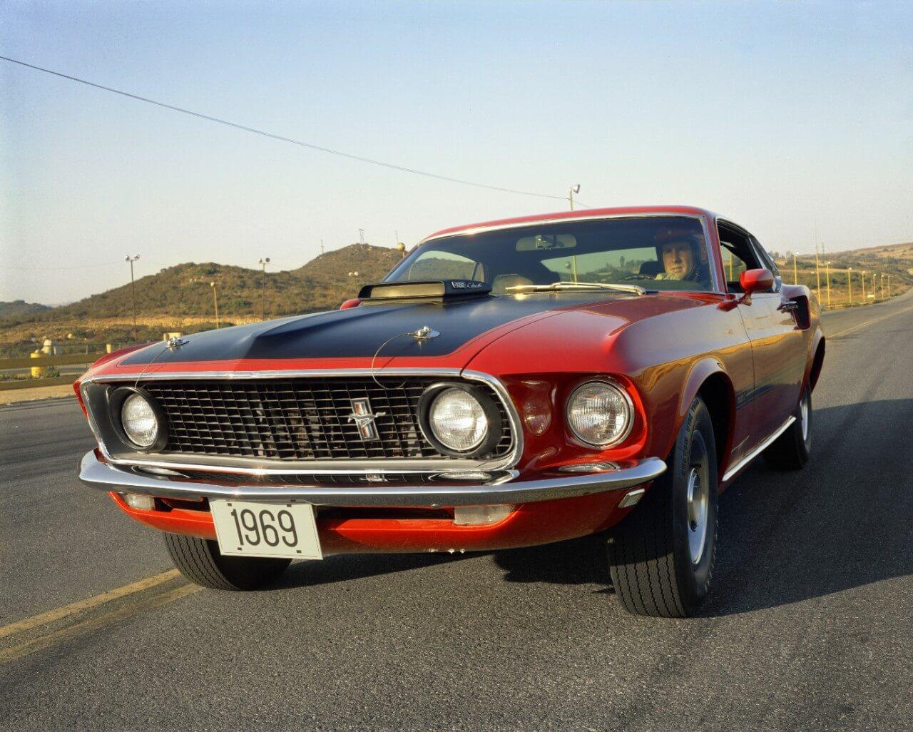 Ford Mustang Mach 1 1969 vermelho com faixa preta sobre o capô e entradas de ar e faróis auxiliares redondos na grade